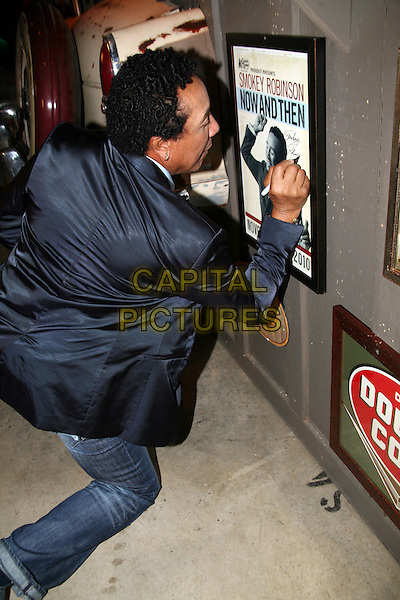 SMOKEY ROBINSON.Smokey Robinson during a visit to the Cracker Barrel Old Country Store corporate offices in Lebanon, TN, USA..October 13th, 2010.full length jeans denim black jacket back behind rear kneeling signing autograph .CAP/ADM/RR.©Randi Radcliff/AdMedia/Capital Pictures.