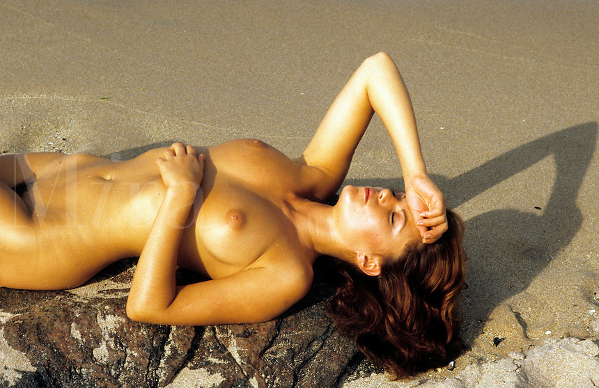 Nude woman sunbathing on beach