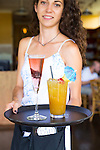 A waitress holds two signature drinks, the Hibiscus Champagne and the Mai Tai at the Hali'imaile General Store Restaurant on the island of Maui, Hawaii
