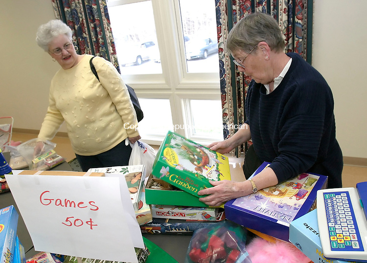 BETHLEHEM, CT, 01 April 2006- 040106BZ12-  Carol Anderson, of Morris, left, looks on as her friend Irene Granoth, of Morris, searches through games at a tag sale at the Church of the Nativity in Bethlehem Saturday.<br />  Jamison C. Bazinet Republican-American