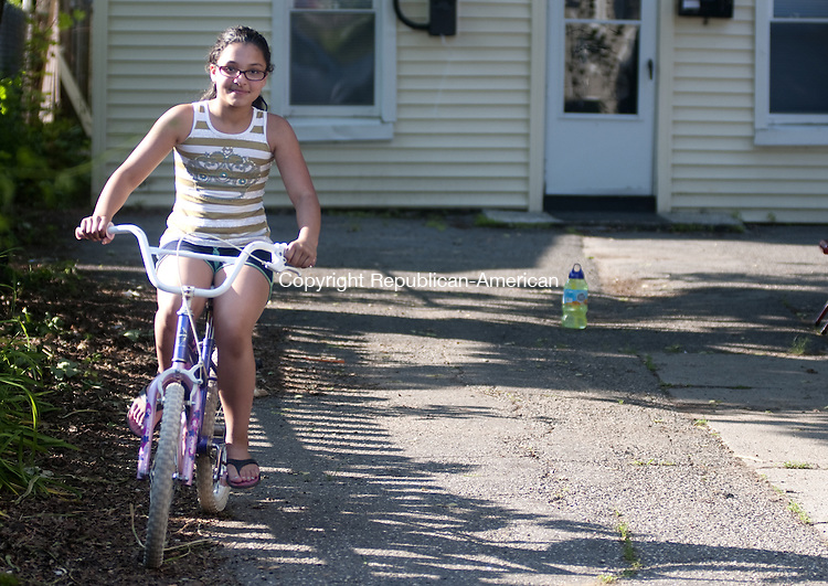 TORRINGTON, CT - 17 JUNE 2014 -- Emma Mabe rides a bicycle given to her Monday by a police officer who investigated the theft of her bike from her Albert Street yard a couple weeks ago. The officer suprised her with the bike Monday.  Alec Johnson/ Republican-American