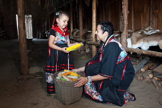 Ojibwe mother and daughter dressed in traditional ribbon dresses with a large basket of corn inside a bark covered longhouse, during a visit to the Huron Ouendat Indian Village in Midland, Ontario.