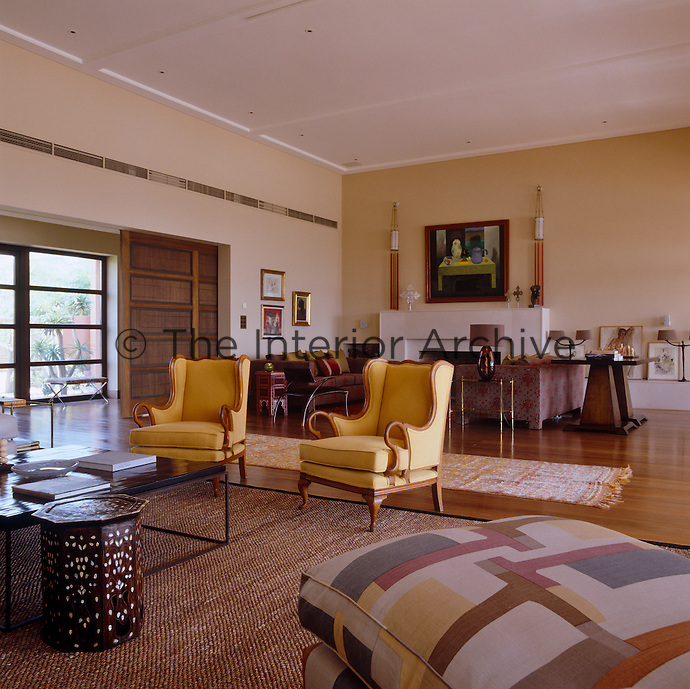 The spacious living room has two distinct seating areas both grouped around low tables on large modern rugs