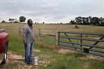 May 22, 2010. Baskerville, Virginia.. John Boyd, Jr. prepares to feed cattle on his farm that the family has owned for over 100 years.. Dr. John Boyd, Jr., a Virginia farmer, has lobbied the White House and Congress for the better part of two decades on behalf of black farmers. .A $1.25 billion settlement he helped to negotiate in February for the federal government to compensate black farmers has become ensnared in Washington. .Meanwhile, many elderly farmers who stand to benefit are dying before they can seek restitution..Their case, known as the black farmers settlement, and commonly referred to as Pigford II, is the second phase of a federal lawsuit settled in 1999. It covers more than 80,000 farmers who claim they were denied critical aid comparable to what white farmers received from the Department of Agriculture between 1981 and 1996 because of the color of their skin..Congress reopened the case in 2008, and set aside $100 million to address the late claims. President Barack Obama, who co-sponsored the 2008 measure when he was in the Senate, created a $1.15 billion line item in his budget for the 2010 fiscal year to cover the new class of litigants..The money was less than half of the $2.5 billion the farmers had fought for, but the administration's promise of a quick resolution prompted them to accept the deal.  .