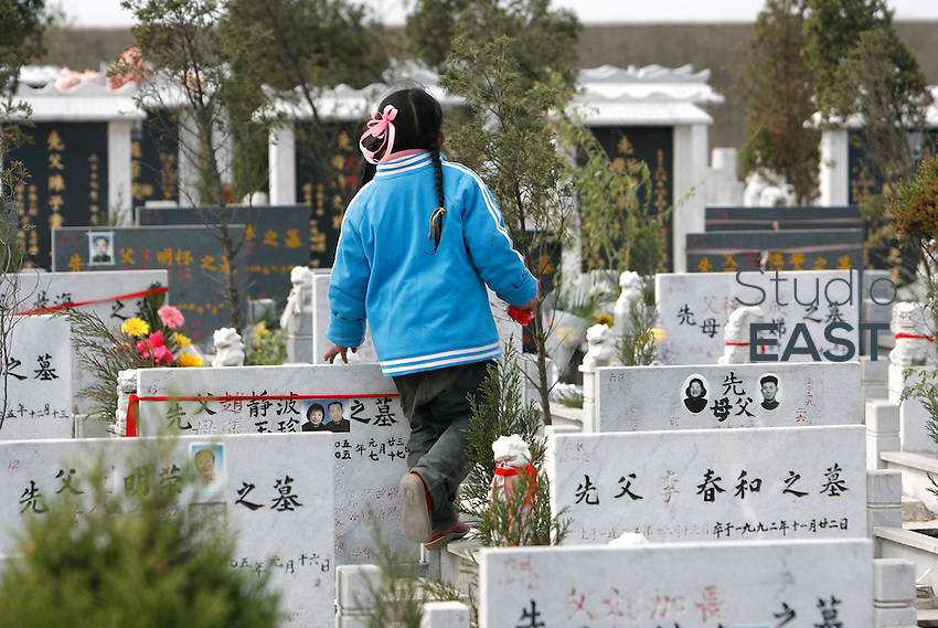 A little girl walks on tombs during Tomb Sweeping day, or 'Qingming', in a cemetery near Nianjing, Jiangsu province, China, on April 4, 2008. The Qingming Festival is a traditional Chinese festival usually occurring around April 5 of the Gregorian calendar. For the Chinese, it is a day to remember and honor one's ancestors at grave sites. Young and old pray before the ancestors, sweep the tombs and offer food, tea, wine, chopsticks, (joss) paper accessories, and/or libation to the ancestors. Photo by Lucas Schifres/Pictobank