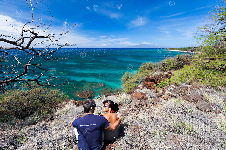 Happy couple sitting along the edge of the trail and enjoying a view of the ocean and coastline of Lahaina, Maui.