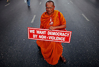 "A Buddhist monk holds a banner as he joins other supporters of former premier Thaksin Shinawatra in central Bangkok March 13, 2010. Anti-government protesters headed for Bangkok from the countryside on Saturday for what they are calling a ""million-man march,"" aiming to paralyse the capital and topple a government they say is a front for unelected elites.  REUTERS/Damir Sagolj (THAILAND)"