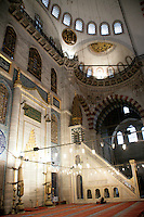 Praying in the Suleymaniye Mosque, Istanbul, Turkey. Both the mihrab and minbar of the mosque can be seen from left to right.
