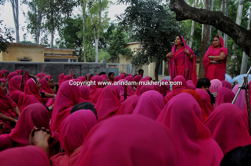 Members of Gulabi Gang listening to Sampat Pal Devi during a meeting at Fatehpur in Uttar Pradesh. Sampat pal Devi the commander of Gulabi Gang fights for women empowerment, justice and rights among the poor people of Bundelkhand region of Uttar Pradesh. Sampat Pal Devi comes from a poor family in Bundelkhand - the poorest region of India. The region is fraught with abject poverty, gross under development, lack of law and order, and stark casteism in which the Brahmins and other higher caste people treat their low caste brethren with disdain. Out of such situation when Sampat Pal Devi decided to speak up for the poor, she has been winning heart felt gratitude of the poor as well as enmity of the high caste people and grudging respect of the law enforcement officials who used to be largely inactive in these badlands of North India. Initially, she began with helping distressed women - victims of domestic violence and dowry system, but soon started getting other cases of nature of land dispute and under development. She emerged as a fiery leader in 2007, when she beat up the OC of the local police station while demanding release of a dalit woman kept locked up in the cell for thirteen days without being charged with a case.Today, she has a huge fan following of some 25 hundreds of thousands of women (spread across 8 districts of the state of UP) who have come to be known as Gulabi Gang or Pink Vigilante Women for their vibrant pink sarees - the costume of the gang; and fiery nature of dealing with injustice. When verbal negotiations for justice fail they resort to beating up. Sampat Devi is viewed as a messiah with the promise of bringing back law and order for the poor, in these mafia troubled areas. Today, perpetrators are simply scared of her as she does not hesitate to challenge law and order and even system - to win justice for the poor. More complaints related to domestic violence and other problems are registered now with the police than they ever used to be. Sh