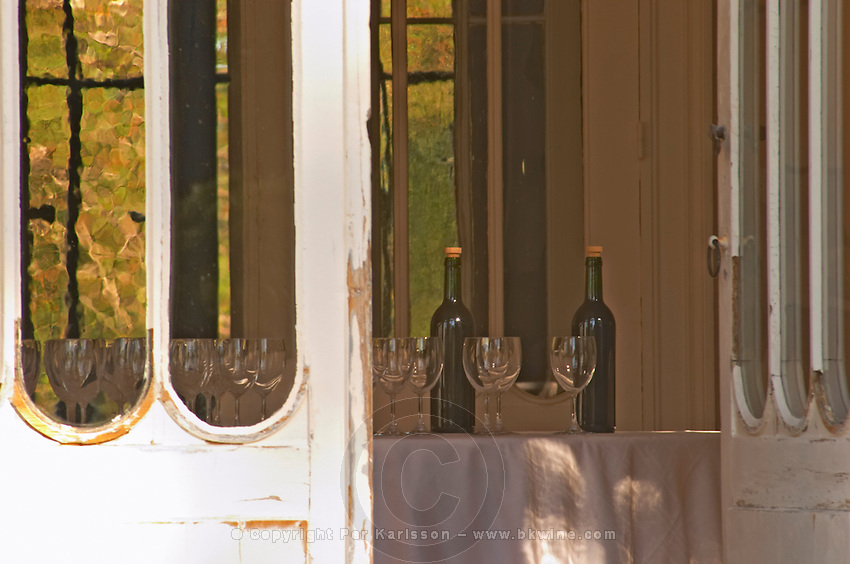 Door open to the garden with inside a table set with glasses and bottles for tasting wine, sunshine and shade, summer - Chateau Belgrave, Haut-Medoc, Grand Crus Classe 1855