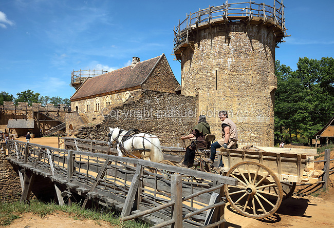 Cart pulled by a horse transporting building materials across a bridge to the building site, and behind, the Great Tower or Tour Maitresse and the North Range or Logis Seigneurial, at the Chateau de Guedelon, a castle built since 1997 using only medieval materials and processes, photographed in 2017, in Treigny, Yonne, Burgundy, France. The Guedelon project was begun in 1997 by Michel Guyot, owner of the nearby Chateau de Saint-Fargeau, with architect Jacques Moulin. It is an educational and scientific project with the aim of understanding medieval building techniques and the chateau should be completed in the 2020s. Picture by Manuel Cohen