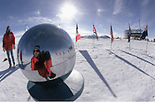 Photographer Ernie Mastroianni snaps a self portrait in the chrome ball that marks the geographic south pole at Amundsen Scott South Pole Station in January, 2001. In the background is the new building for the US station.