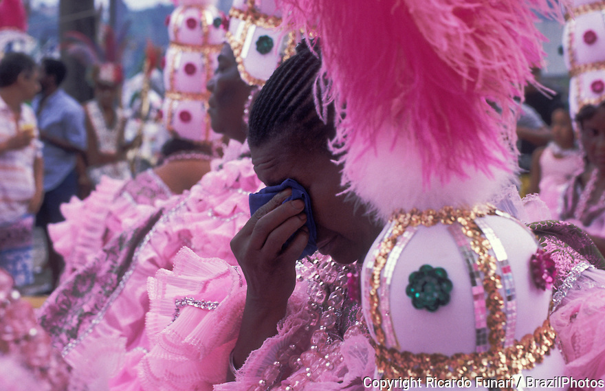 Samba schools parade, end of party -  baiana, elderly black woman wearing pink costumes from Mangueira Samba School cries at the end of the parade at dawn - emotion - Rio de Janeiro carnival, Brazil.