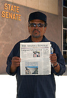 "AJ Alexander - Tomas Alejo (cq) 64 from California holds todays paper with the ""5 migrant bills rejected"" headline at the Arizona State Capitol on Friday March 18, 2011..Photo by AJ Alexander .All Rights Reserved"
