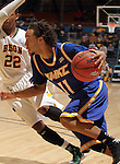 SIOUX FALLS, SD - MARCH 10:   Estan Tyler #11 from UMKC drives against Kory Brown #22 from North Dakota State University in the second half of their semifinal game Sunday evening at the 2013 Summit League Basketball Tournament in Sioux Falls. SD. (Photo by Dave Eggen/Inertia)