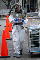 A medical worker wearing a protective hood carries a patient sample back to the testing tent as part of COVID-19 drive-through testing in a parking lot near the Cambridge Health Alliance Women's Health Hospital in Somerville, Massachusetts, on Mon., March 23, 2020. Patients could make appointments to drive through the parking lot to get tested for the virus during the ongoing Coronavirus (COVID-19) global pandemic. This location is one of a handful of such testing facilities that have opened in the Boston area in the past week.