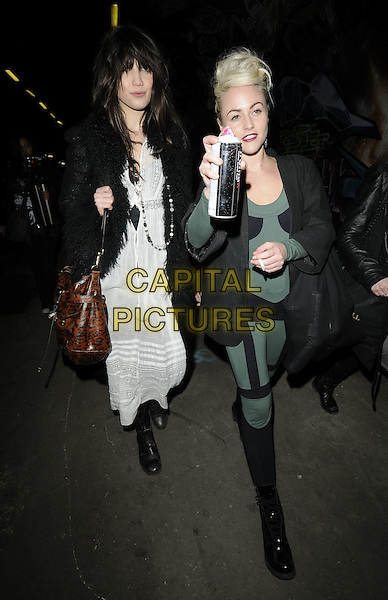 DAISY LOWE & JAIME WINSTONE.Leaving the UK film premiere for Banksy's 'Exit Through The Gift Shop', at Leake Street Tunnel, Waterloo, London, England..March 1st 2010 .arrivals full length black green jumpsuit catsuit Pam Hogg jacket patent heeled lace-up boots spray paint can holding bag patches costume Jamie grey gray cigarette long white dress cotton cheesecloth spray spraying black fur trim coat maxi boots bag brown animal Mulberry print leopard lace-up peasant.CAP/CAN.©Can Nguyen/Capital Pictures.