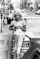 New York, New York USA, June 1979 - French singer Sylvie Vartan sits on the hood of a car with her dog, Sniff  She recently released her first album in the US and was in New York City to promote it.