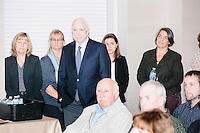 Arizona senator and former Republican presidential nominee John McCain listens as Republican presidential candidate and South Carolina senator Lindsey Graham speaks at a town hall at the offices of McLane Middleton Law Firm in Manchester, New Hampshire.  McCain also spoke at the event and joined Graham for other events throughout the state over the following two days.