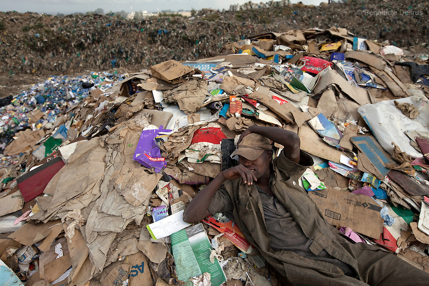 13 february 2013 - Dandora dumpsite, Nairobi, Kenya - A Kenyan man takes a break from scavenging for recyclable materials at the Dandora dumpsite, one of the largest and most toxic in Africa. Located near slums in the east of the Kenyan capital Nairobi, the open dump site was created in 1975 and covers 30 acres. The site receives 2,000 tonnes of unfiltered garbage daily, including hazardous chemical and hospital wastes. It is a source of survival for many people living in the surrounding slums, however it also harms children and adults' health in the area and pollutes the Kenyan capital. Photo credit: Benedicte Desrus