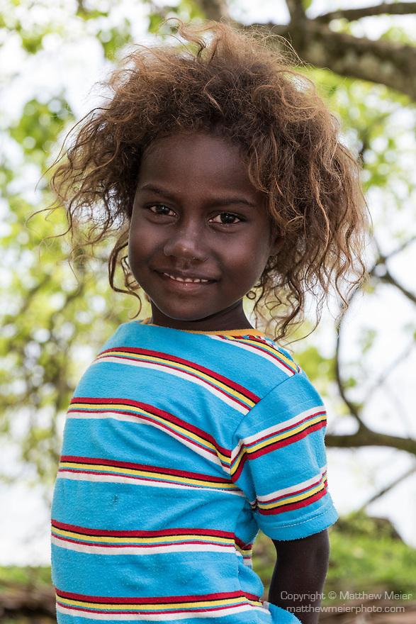 Peava Village, Gatokae Island, Solomon Islands; a young girl poses for a photo under a tree along the shoreline