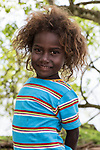 Peava Village, Gatokae Island, Solomon Islands; a young girl poses for a photo under a tree along the shoreline
