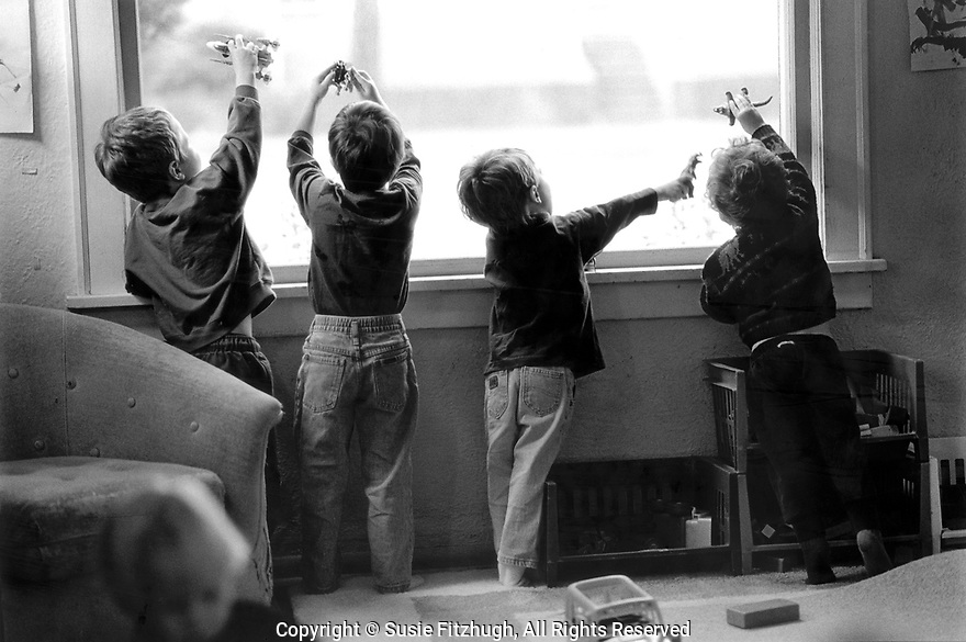 Boys in a home-based daycare setting play with their small toys against the light of a window,