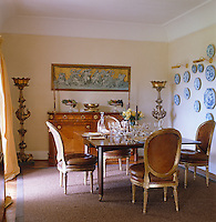 The traditional dining room is furnished in a mixture of styles and periods and one wall is decorated with a collection of blue and white plates