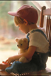 young boy sitting on chair talking to teddy bear