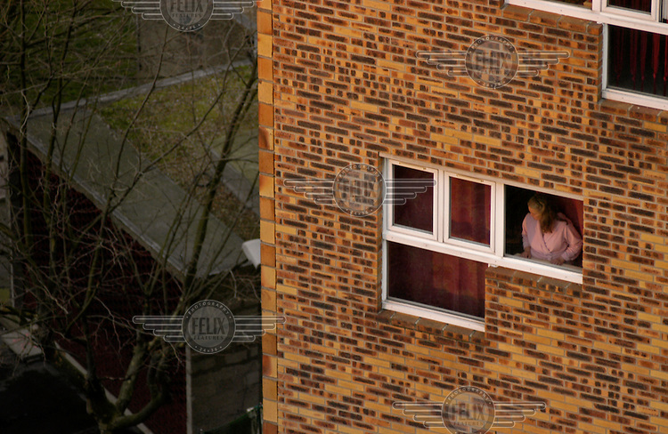 A resident of a banlieue housing project peers out of her window in Pantin.