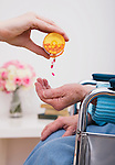 Young woman giving pills to senior woman, close-up of hands