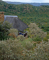 The thatched roof house, although well hidden by surrounding scrub, sits high in the hills and has spectaular views from its terraces