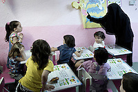 A Koran class held in the basement of a house rented by a Kuwati businessman on behalf of Syrian widows and their children. The eldest refugee children enroll in local schools but the youngest are taught in the house. Approximately two million people have fled the conflict in Syria since it began in 2011, with nearly half a million in Jordan.