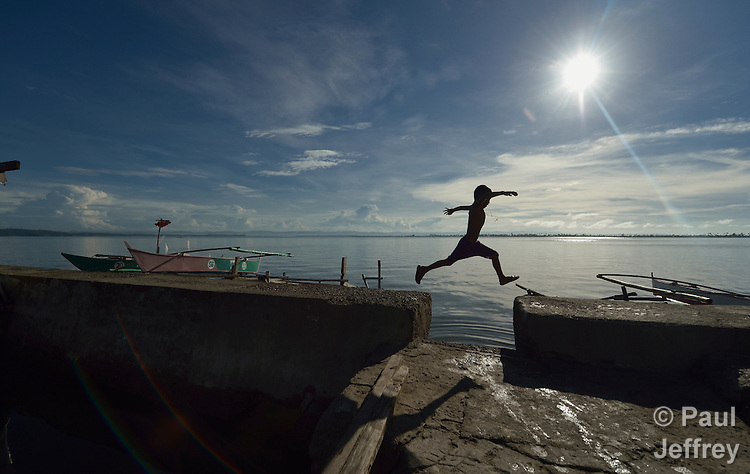 Seven-year old Mark Dave Mortiga, nicknamed Pipoy, jumps a gap in a walkway along the sea in Tacloban, a city in the Philippines that was hard hit by Typhoon Haiyan in November 2013. Known locally as Typhoon Yolanda, the storm surge buried this area with water, destroying the neighborhood. Despite a government prohibition on rebuilding within 40 meters of the shoreline, residents say they have nowhere else to go and have constructed new dwellings over the water. The ACT Alliance has accompanied survivors in this neighborhood and other areas impacted by the typhoon as they rebuild their communities and livelihoods.