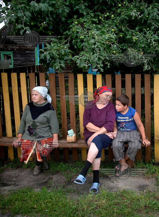 A woman and one of her grandchilden sit together in a small village that was affected by the Chernobyl nuclear disaster.