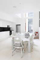 A clean white contemporary kitchen/dining area has been created in the basement of the house with a double height atrium to the rear