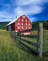 Warren County, VA<br /> Weathered red barn with wooden fence below the ridge line of the Shenandoah mountains
