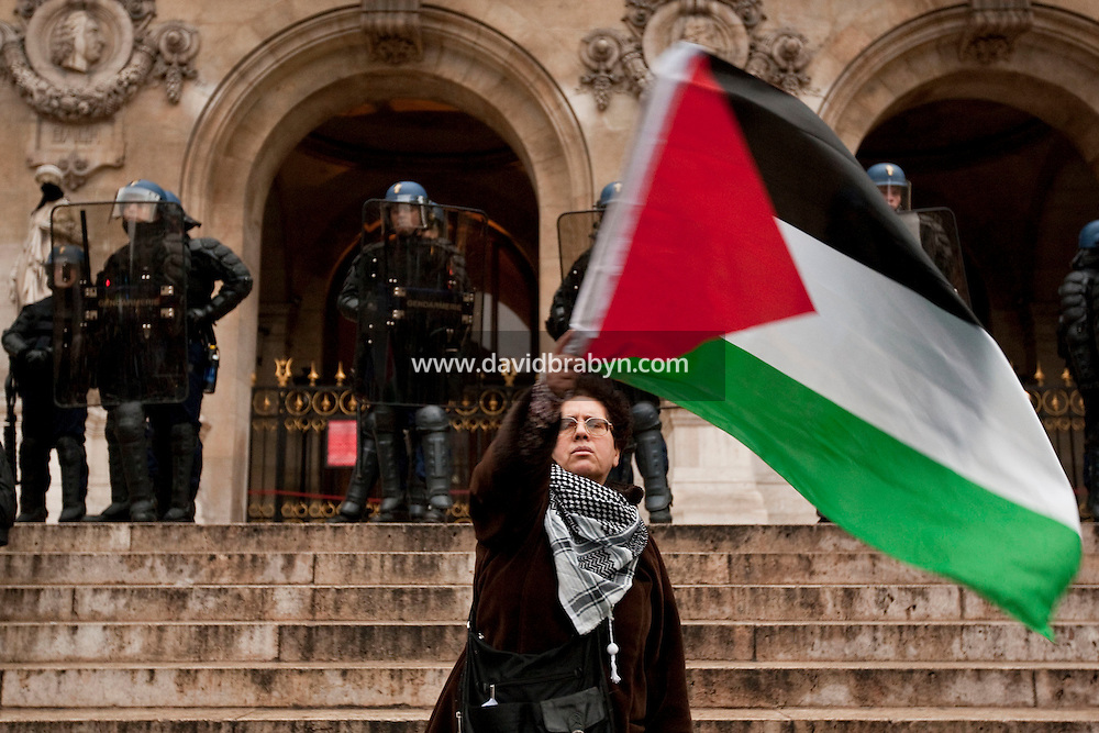 A woman stands waving a Palestinian flag in front of a cordon of riot police blocking access to the Palais Garnier opera house in Paris, France, 17 October 2009, during a protest by several thousand people against Israel's military offensive in the Palestinian Gaza Strip.