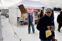A person dressed as a pig advertises barbecue food at a vendor's tent at the Whitefish Skijoring World Championship event in Whitefish, Montana, USA.  Skijoring is a competitive sport in which a person on skis navigates an obstacle course while being pulled behind a galloping horse.