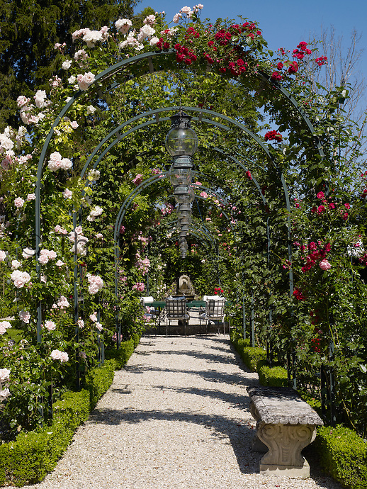 A gravel path in the garden garlanded with red and pink roses leads to a secluded seating area