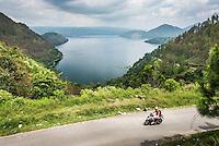 Tourist exporing Lake Toba (Danau Toba) by motorcycle, North Sumatra, Indonesia