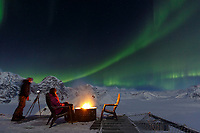 Two women watch the Northern Lights (Aurora Borealis) while sitting on the deck around a campfire at the Sheldon Chalet in the Ruth mphitheater in the Alaska Range.  Winter  <br /> <br /> Photo by Jeff Schultz/SchultzPhoto.com  (C) 2017  ALL RIGHTS RESERVED