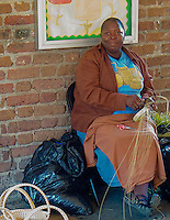 Within Charleston, South Carolina, Public Market are many vendors and craftspeople, like this basket weaver plying her trade.