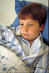 sick young boy in bed with thermometer in mouth