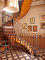An elegant curving staircase in a hallway decorated in gold and yellow.