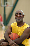 Smiling African American man holding basketball