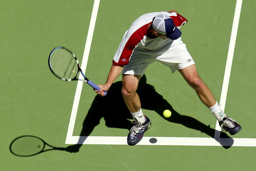 Andy Roddick plays a difficult shot between his legs during the Australian Open.