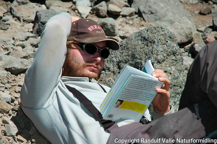 Mann leser bok i base camp, Plaza de Mulas, Aconcagua. ---- Man reading in base camp, Plaza de Mulas, Aconcagua.