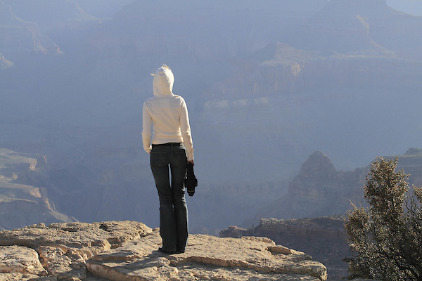 Thin woman standing on the edge of the South Rim of Grand Canyon National Park, Arizona. . John offers private photo tours in Grand Canyon National Park and throughout Arizona, Utah and Colorado. Year-round.