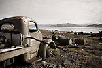 Remains of old vehicles and other military garbage rust into the Canadian Tundra, Nunavut, Canada. In the background the landscape and pristine snow covered mountains of Baffin Island.